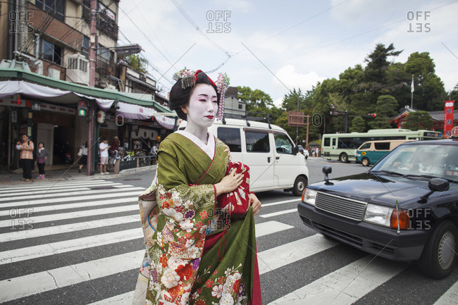 A woman dressed in the traditional geisha style, wearing a kimono and obi with bright red lips and dark eyes crossing a street.