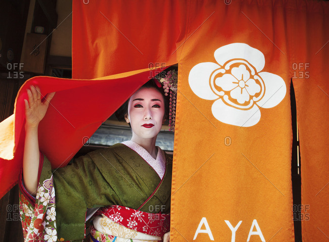 A geisha emerging from a door lifting up the curtain, in traditional kimono and makeup.