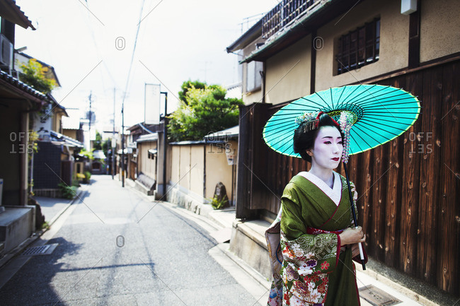 A woman dressed in the traditional geisha style, wearing a kimono and obi with bright red lips and dark eyes holding a paper parasol walking along a street