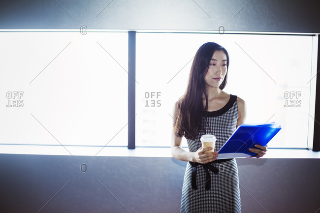 A business woman by a window with a view over the city, holding a cup of coffee and a folder.