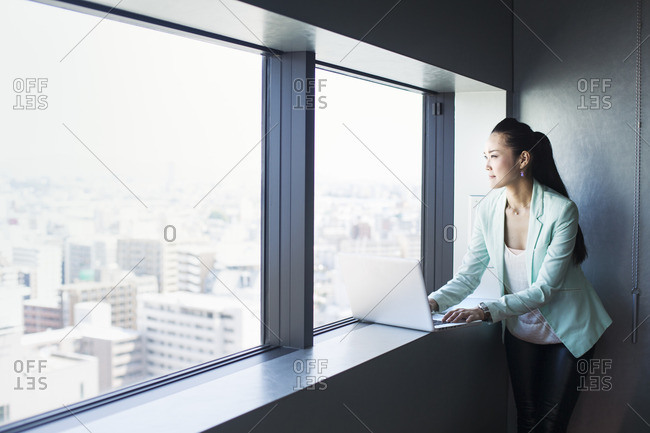 A business woman by a window with a view over the city, looking out. Laptop.