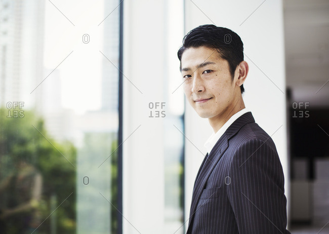 A businessman in the office, by a large window, looking at the camera.