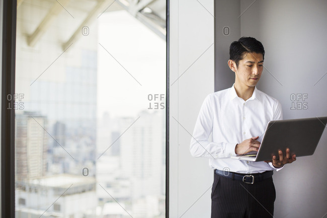 A business man standing by a window with a city view, using his laptop.