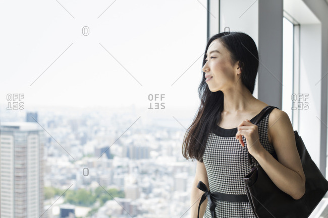 A business woman by a window with a view over the city,