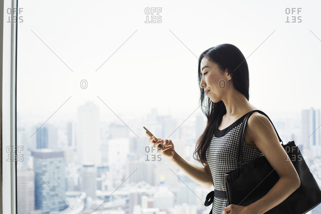 A business woman by a window with a view over the city, using her smart phone.