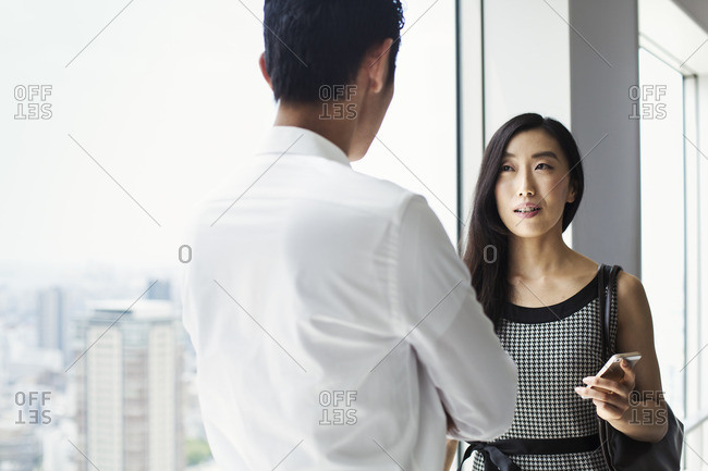 A businessman and businesswoman standing talking by a large window with view over a city