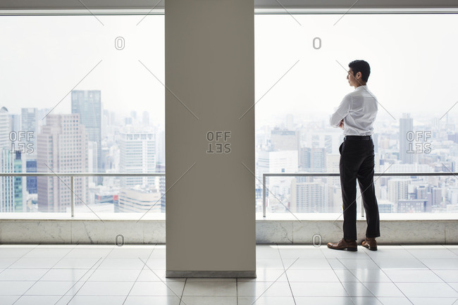 A businessman in the office standing by a large window with arms folded, looking over the city.