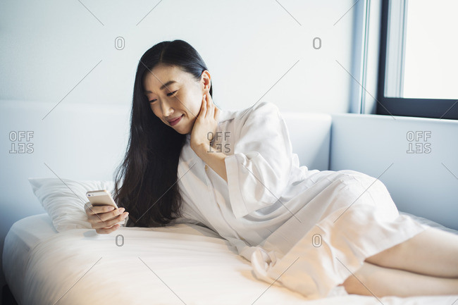 A business woman preparing for work, waking up and checking her smart phone in bed.