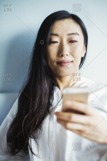 A business woman preparing for work, sitting in bed using her smart phone.