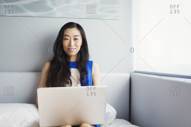 A business woman preparing for work, sitting on a bed using her laptop computer.