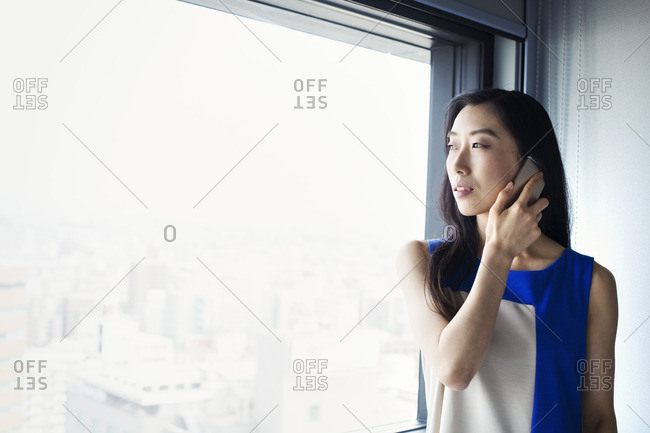 A business woman using her smart phone and standing by a window.