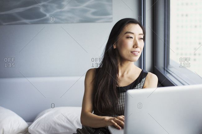 A business woman dressed, sitting on her bed using a laptop.