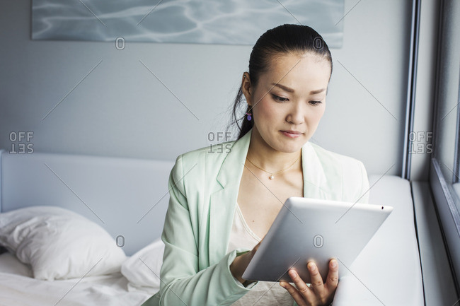 A business woman preparing for work, sitting on a bed using a digital tablet.