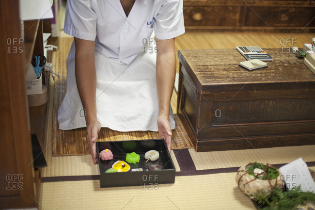 A chef presenting a tray of selected wagashi of different shapes and flavours.
