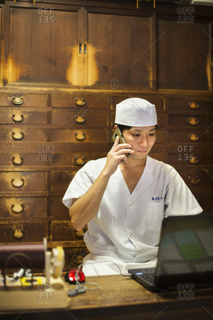 A cook using a laptop and making a phone call at a desk.