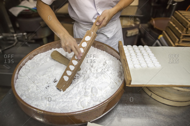 A woman chef mixing a large bowl of ingredients and pressing the mixed dough into moulds in a commercial kitchen.