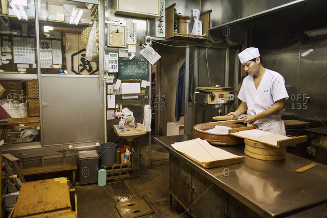 Japan - August 23, 2016: A man mixing a large bowl of ingredients and pressing the mixed dough into moulds in a commercial kitchen.