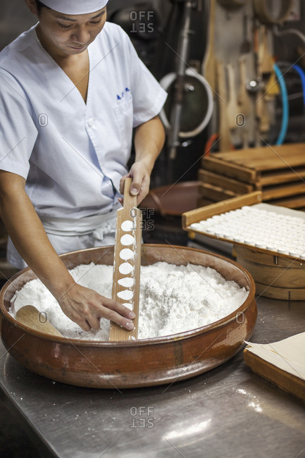 A man mixing a large bowl of ingredients and pressing the mixed dough into moulds in a commercial kitchen.