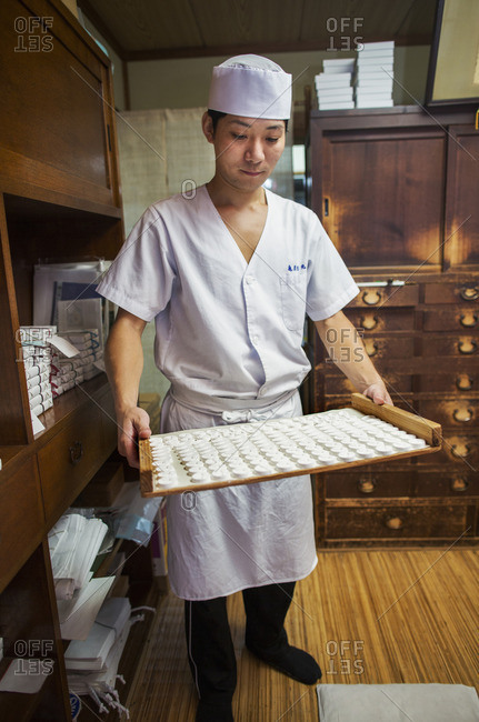 A small artisan producer of specialist treats, sweets called wagashi. A man holding a tray of sweets.