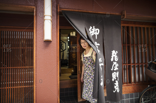 Japan - August 23, 2016: A woman at the doorway of the shop.