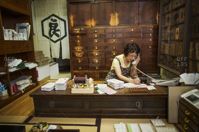A traditional wagashi sweet shop. A woman working at a desk using a laptop and phone.