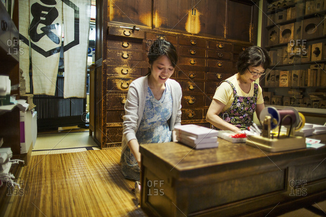 A traditional wagashi sweet shop. A woman working at a desk using a laptop and phone