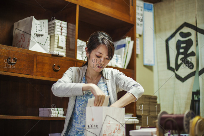 A small artisan producer of specialist treats, sweets called wagashi. A woman working packing sweet boxes for delivery.