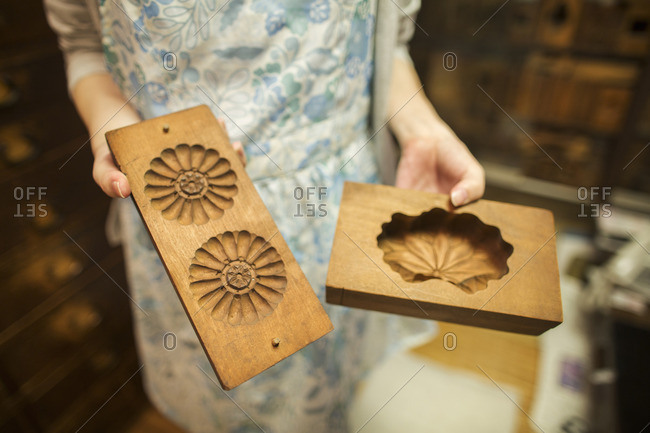 A small artisan producer of specialist treats, sweets called wagashi. A woman holding shaped wooden moulds used in the production of sweets.
