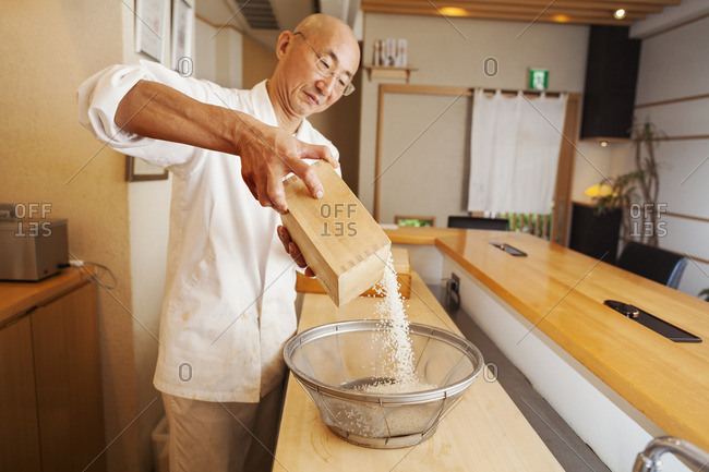 A chef working in a small commercial kitchen, an itamae or master sushi chef preparing rice for cooking.