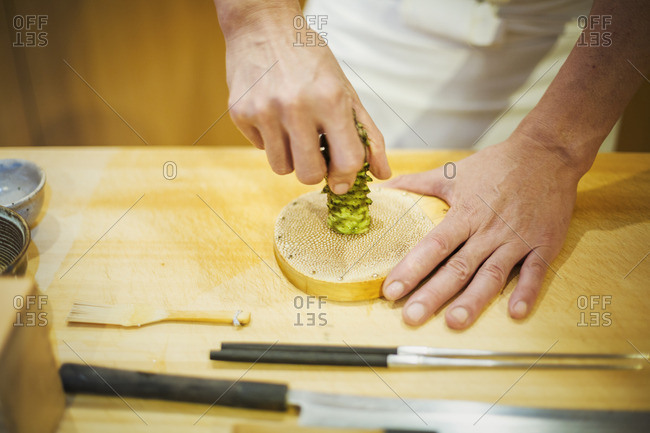 A chef working in a small commercial kitchen, an itamae or master chef grating horseradish root for wasabi.