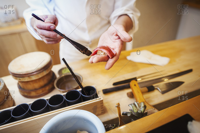 A chef working in a small commercial kitchen, an itamae or master chef making sushi, pasting sauce on fish.