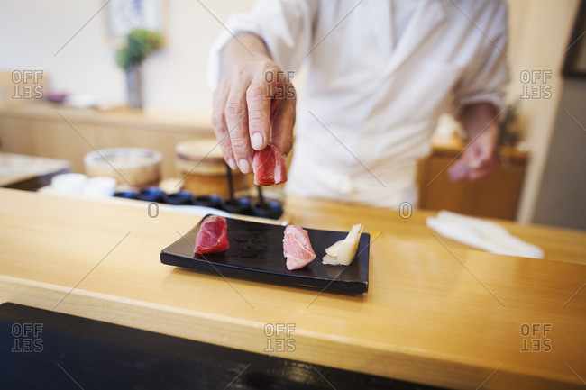 A chef working in a small commercial kitchen, an itamae or master chef presenting a fresh plate of sushi.