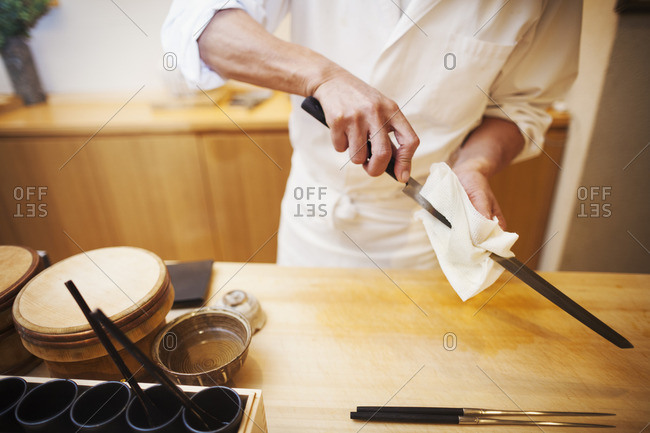 A chef working in a small commercial kitchen, an itamae or master chef preparing to make sushi, cleaning his knife.