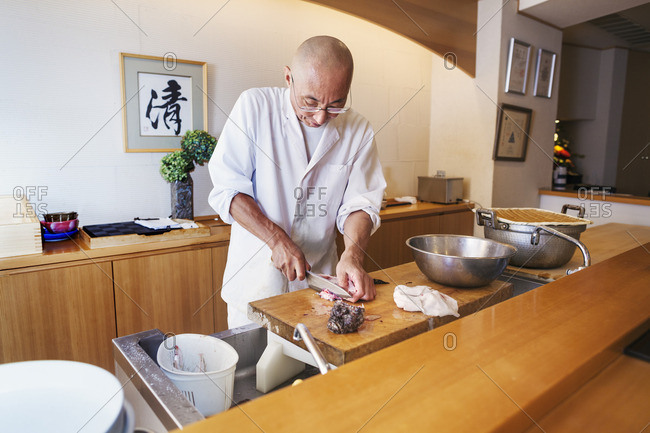 A chef working in a small commercial kitchen, an itamae or master chef slicing fish with a large knife for making sushi