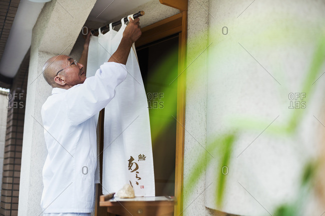 A chef in a small commercial kitchen, an itamae or master chef drawing a curtain across a door.
