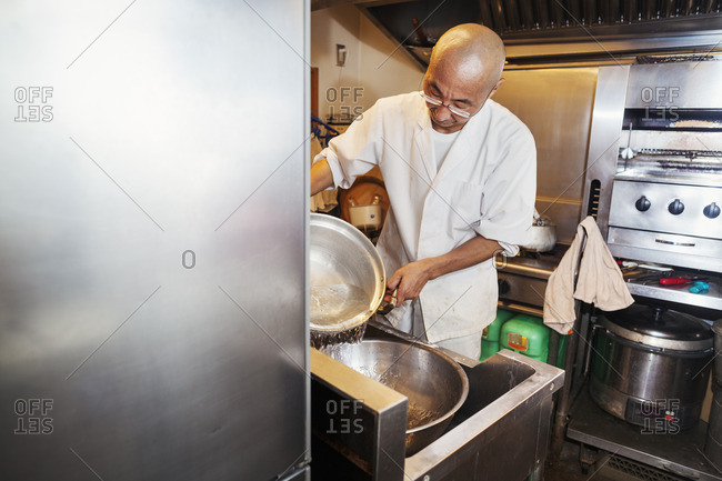 A chef working in a small commercial kitchen, an itamae or master chef making sushi. Preparing rice for the dishes.