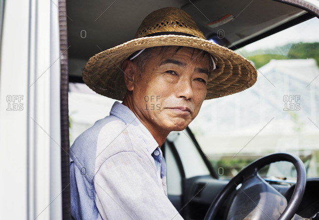 A man in a hat sitting in the driving seat of a truck.