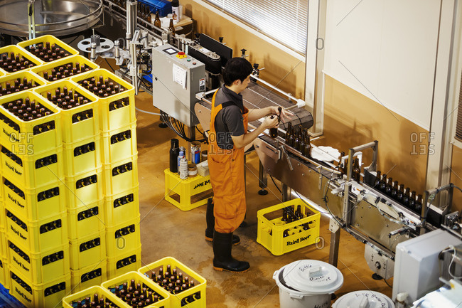 Japan - August 3, 2016: Worker standing next to yellow plastic crates with beer bottles in a brewery.