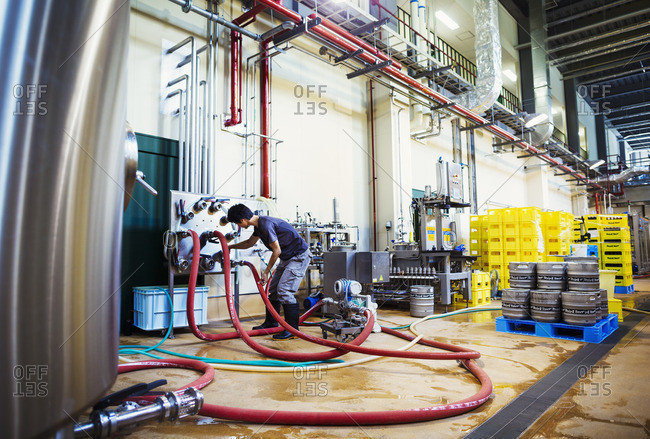 Japan - August 4, 2016: Man working in a brewery, connecting hoses to a metal beer tank.