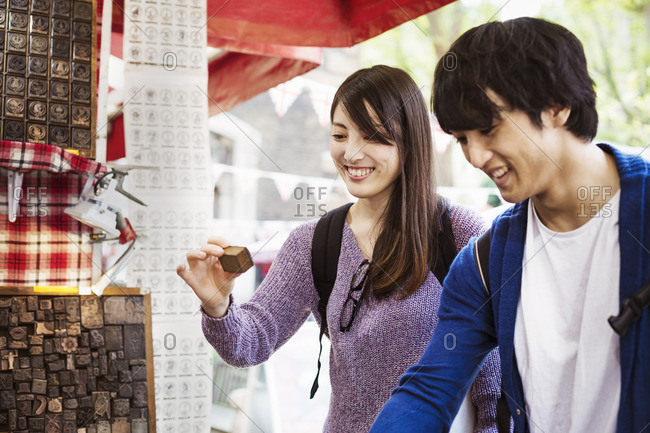 Two Japanese tourist shopping at a street stall.