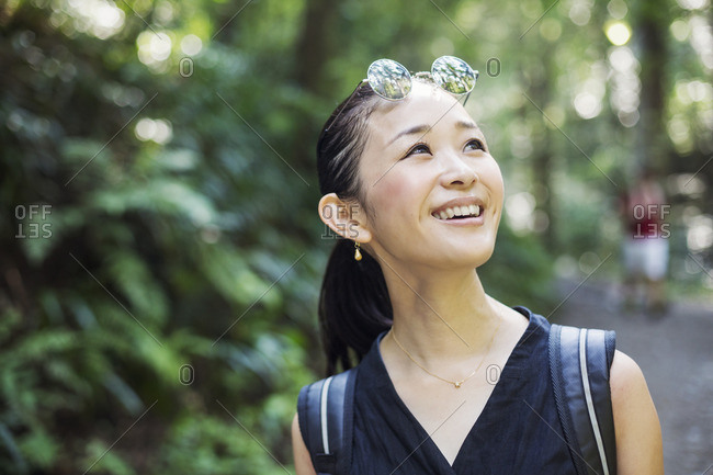 Portrait of a smiling young woman standing in a forest.