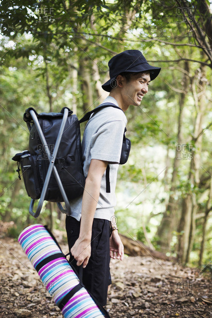 Man standing in a forest, carrying a picnic rug and backpack.
