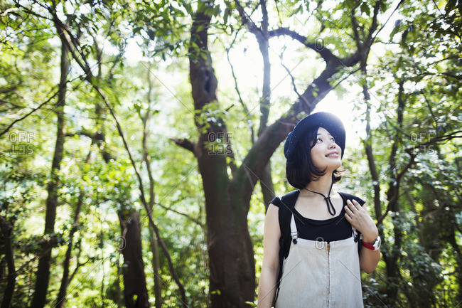 Young woman standing in a forest.
