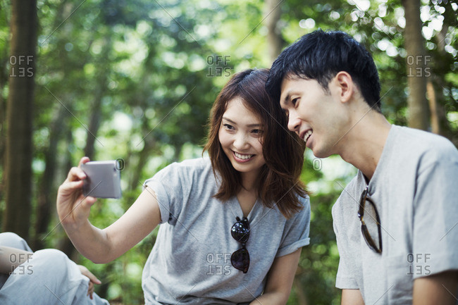 Young woman and a man sitting in a forest, taking a selfie.
