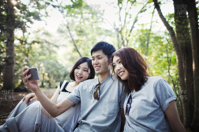 Two young women and a man sitting in a forest, taking a selfie.