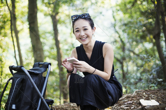 Smiling young woman sitting in a forest.