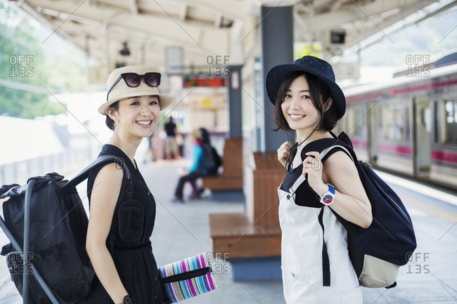 Two young women standing on a platform at a railway station.