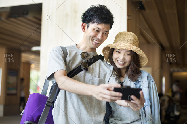 Young woman and man standing outdoors, taking selfie.