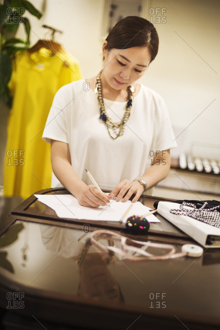 Woman working in a fashion boutique in Tokyo, Japan, writing.
