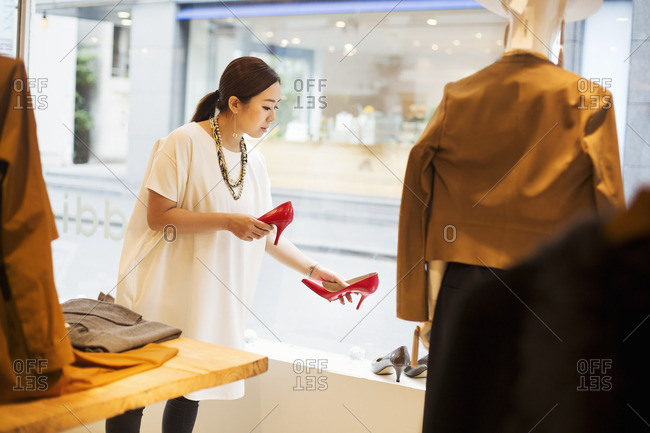 Woman working in a fashion boutique in Tokyo, Japan, holding a pair of red high heels.